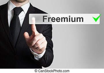 businessman pushing flat button freemium green checked