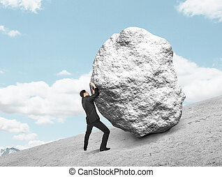 businessman pushing stone up on hill