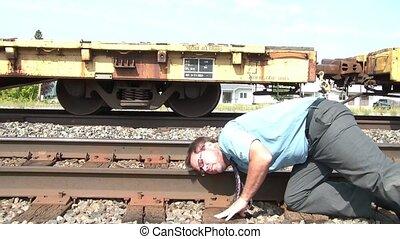 Businessman Puts Ear to Railroad Track