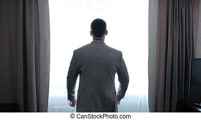 businessman puts on a suit