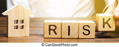 Businessman puts wooden blocks with the word Risk and a house. Real estate investment risk. Risky investments. Loss of property for non-payment. Debts. Mortgage tax. Fraudulent schemes. Property
