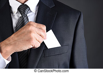 Businessman putting a blank business card into his jackets breast pocket