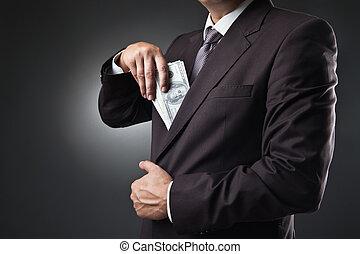 businessman putting money in his pocket on dark