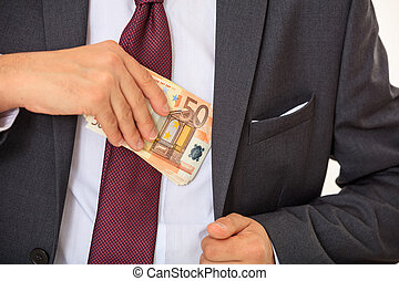 Businessman putting money in his suit