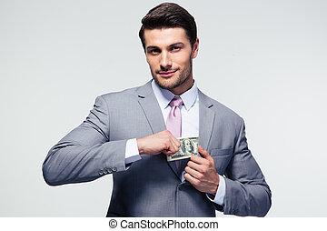 Businessman putting money in pocket over gray background. ...