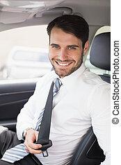 Businessman putting on his seat belt