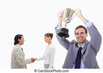 Businessman raising cup with hand shaking colleagues behind...