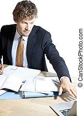 Businessman reaching for laptop at work