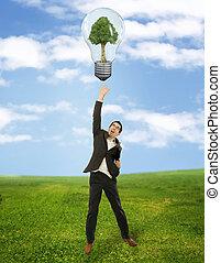 Businessman reaching green energy
