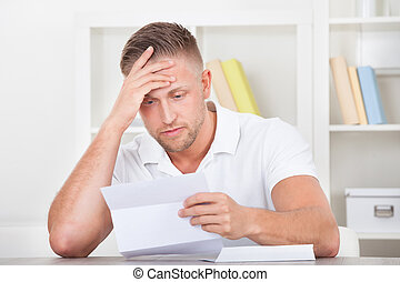 Businessman reacting in shock to a letter