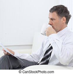 businessman reading a document while sitting in a chair in the hotel room.