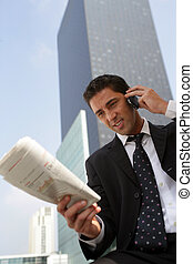 Businessman reading a newspaper in the city