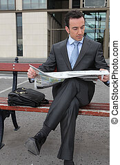 Businessman reading a newspaper on a bench