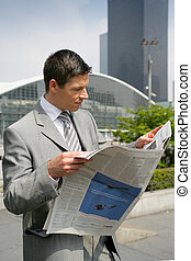 Businessman reading a newspaper outdoors