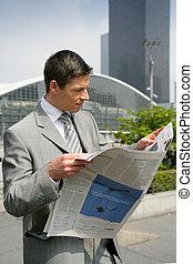 Businessman reading a newspaper outdoors
