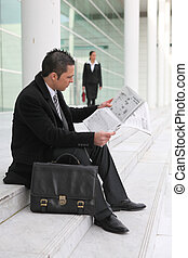 Businessman reading a newspaper outside an office building