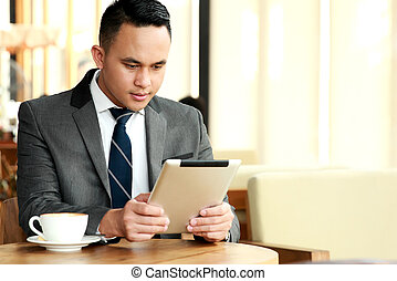 businessman reading an article on his tablets