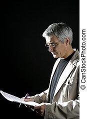 businessman reading at work, senior gray hair