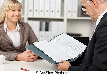 Businessman Reading Candidate'S Cv At Desk