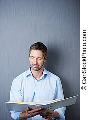 Businessman Reading In Binder Against Blue Wall