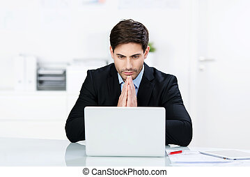 Businessman reading information on his laptop