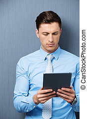 Businessman reading information on his tablet