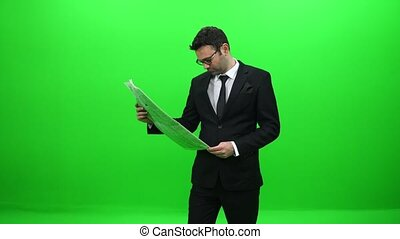 Businessman Reading Newspaper in Front of Green Screen