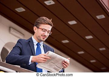 Businessman reading newspaper on station
