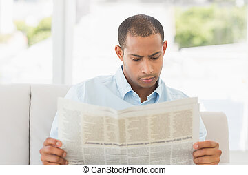 Businessman reading newspaper on the couch