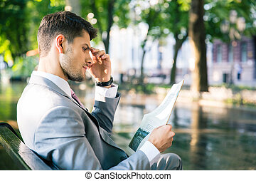 Businessman reading newspaper - Thoughtful businessman...