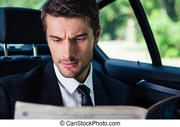 Businessman reading newspaper while riding in car