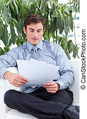 Businessman reading papers on a sofa