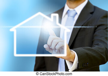 Businessman drawing a house with his fingers on a digital screen