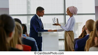 Businessman receiving award from businesswoman in the ...