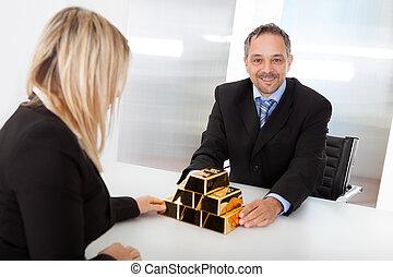 Businessman receiving gold bars
