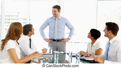 Businessman receiving praise from his employees at meeting...