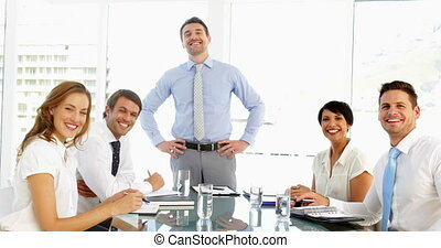 Businessman receiving praise from his staff at meeting and...