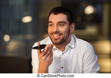 businessman recording voice message on smartphone