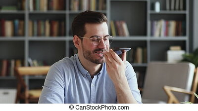 Smiling young man recording voice recognition message on speakerphone. Businessman using virtual assistant app sets reminder on smart phone at home office. Digital ai mobile assistance tech concept