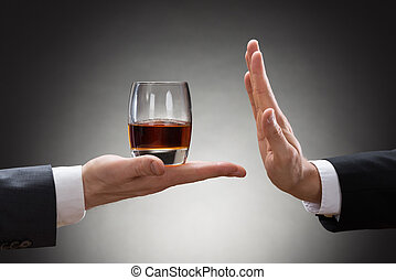 Businessman Rejecting Whisky Offered By Businessperson -...