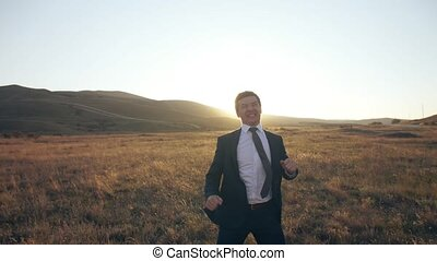 Businessman rejoices and jumps on nature