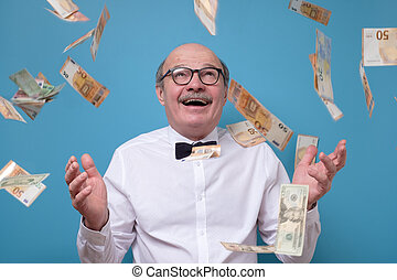Businessman rejoicing for his success with banknotes flying in the air