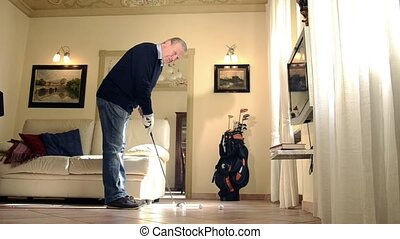 Businessman relaxing at home - senior man practicing golf in...