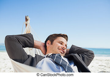 Businessman relaxing in hammock