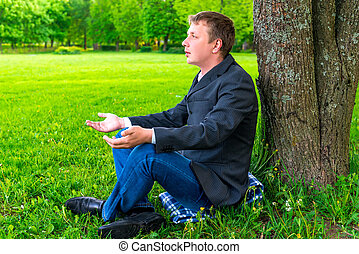 Businessman relaxing in the park near the tree