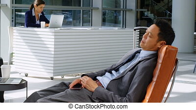 Businessman relaxing on sofa in reception 4k - Businessman...