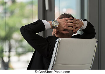 Businessman Relaxing With His Hands Behind His Head