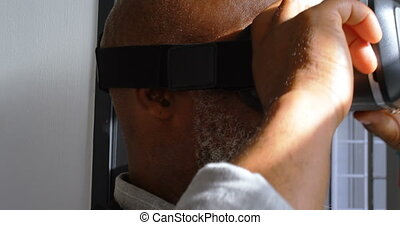 Businessman removing virtual reality headset in the office...