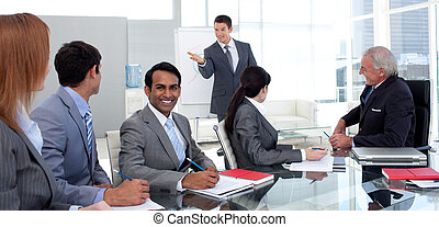 Businessman reporting sales figures to his team in the ...