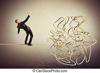 Businessman balancing attempts to get to tangle